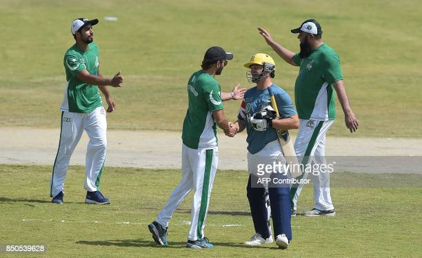 UK Media XI cricketer shakes hands with Pakistan XI cricketer Shahid Afridi after Pakistan XI T20 cricket match victory at the Younis Khan Cricket...
