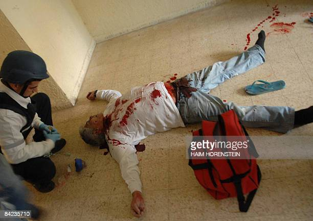 OUT A medic crouches over the body of an Israeli man after he was killed in a rocket attack launched from the Gaza Strip and hit the southern Israeli...
