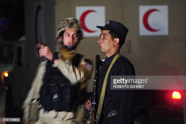 A medic of an Afghan special forces unit confers with a policeman in front of a military ambulance near the security perimeter of the Serena hotel in...