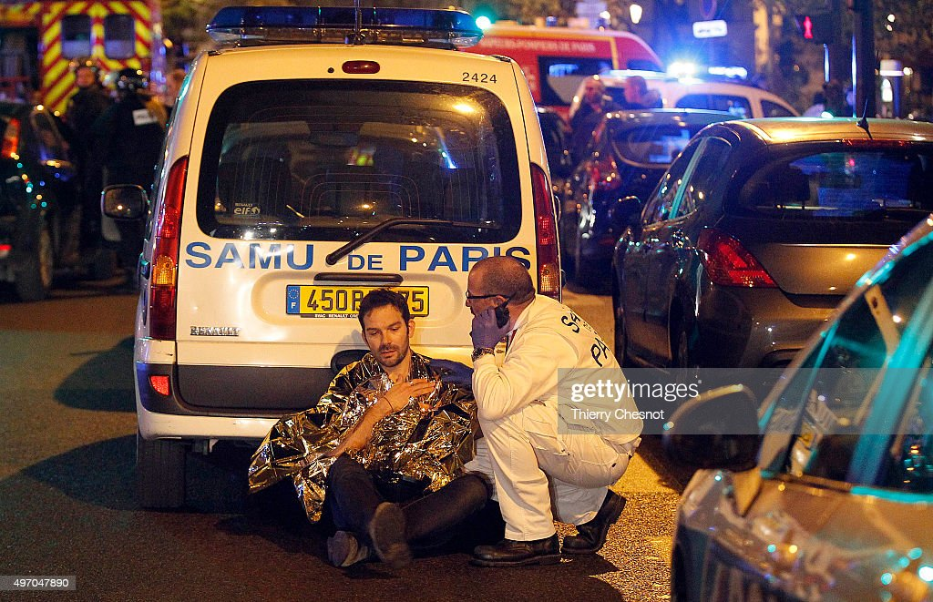 A medic tends to a man after an attack near the Boulevard des FillesduCalvaire November 13 2015 in Paris France Gunfire and explosions in multiple...