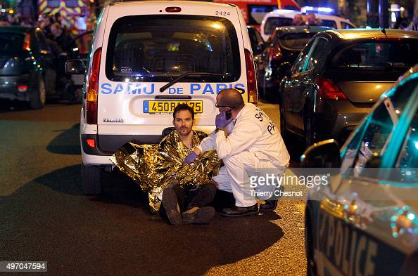 A medic tends to a man near the Boulevard des FillesduCalvaire after an attack November 13 2015 in Paris France Gunfire and explosions in multiple...