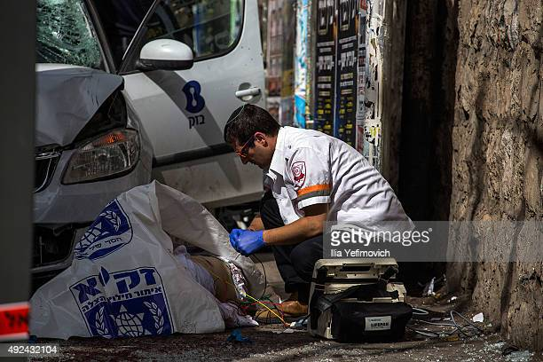 A medic treats a man at the scene of a stabbing attack on October 13 2015 in Jerusalem Israel Tensions in the area continue to run high following...