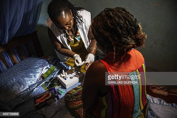 A medic with Doctors Without Borders tests for HIV a sex worker in her room along the Beira 'corridor' on October 17 2014 in Beira Mozambique The...
