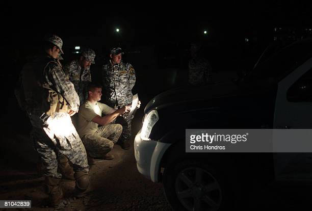 A medic with the 10th Mountain Division looks over Xrays by the light of car headlights to help an Iraqi national police member who was shot by...