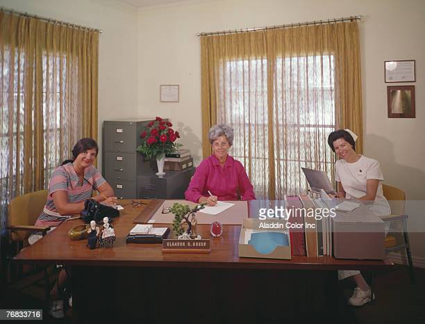 Medical administrator Eleanor H Green sits at her desk a secretary on one side and a nurse on the other in her office at an unidentified medical...