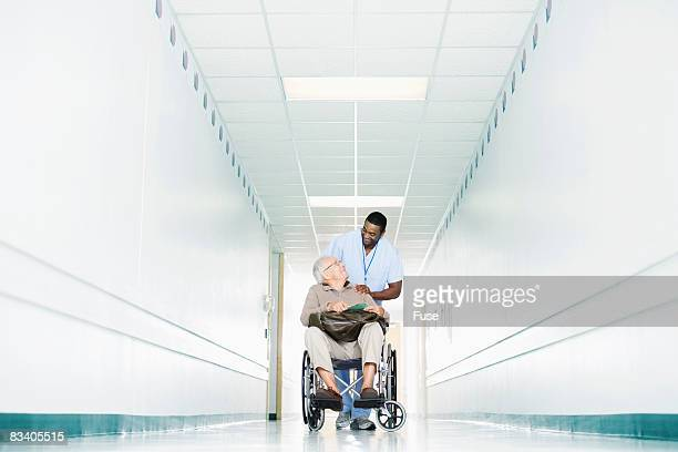 Medical Assistant Talking with Patient in Hallway