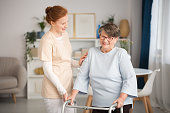 Professional medical caretaker in uniform helping smiling senior woman with a walker in a living room of private luxury healthcare clinic