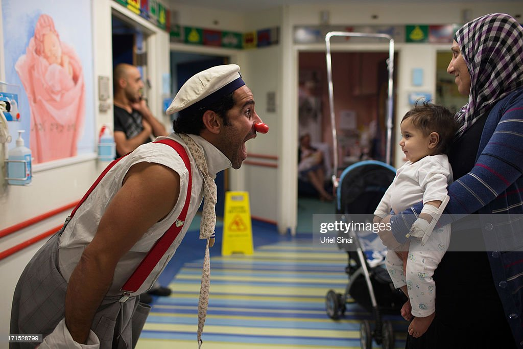 Medical clown David Barashi 'DuSH the clown' interacts with a child as he receives medical care as part of the 'Dream doctors project' at the Hadasa hospital on June 24, 2013 in Jerusalem, Israel. Dream Doctors project integrates professional medical clowning into the medical services provided at Israeli hospitals. Established in 2002, Dream Doctors now operates at 20 hospitals throughout the country.