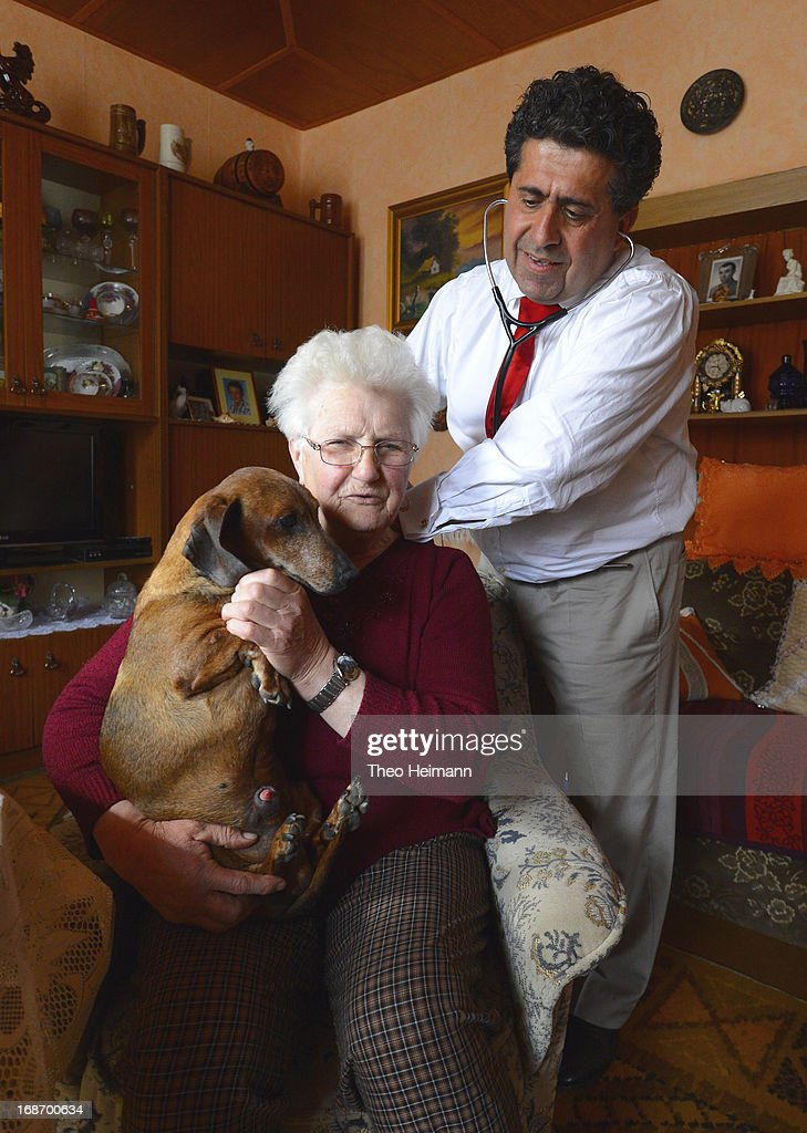 Medical doctor Amin Ballouz uses a stethoscope to listen to the breathing of Cristel Krause, 85, as she clutches her dachshund named Waldi, 17, during a housecall on April 30, 2013 in the village of Gratz an der Oder near Schwedt, Germany. Ballouz was born in Lebanon and moved to Germany as a child, and has had a general practitioner's practice in the small, east German town of Schwedt since 2010. Many of his patients are elderly and live in small villages in the region around Schwedt and Ballouz travels daily in one of his five Trabant cars to pay housecalls. Eastern Germany faces a chronic shortage of country doctors to serve rural communities.