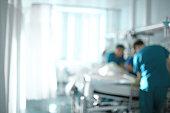 Medical doctor team at the bedside of patient, unfocused background.