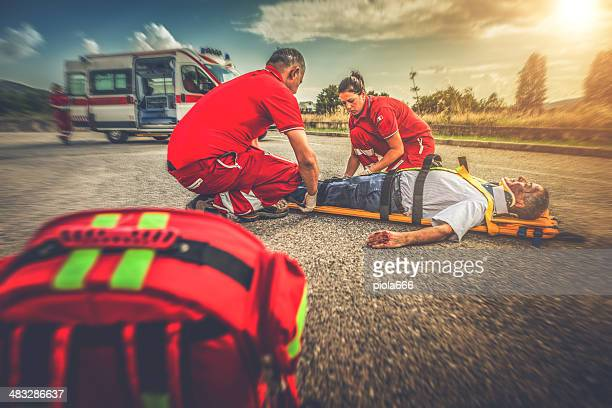 Medical emergency team soccurring man at street accident