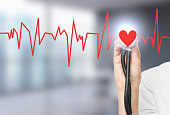 hand listening to a red heart with a phonendoscope, the heart is a part of a cardiogram. Blurred office background. Concept of medical examination.