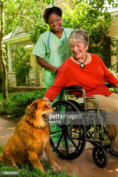Medical:  Happy caregiver and patient pause to pet the dog.