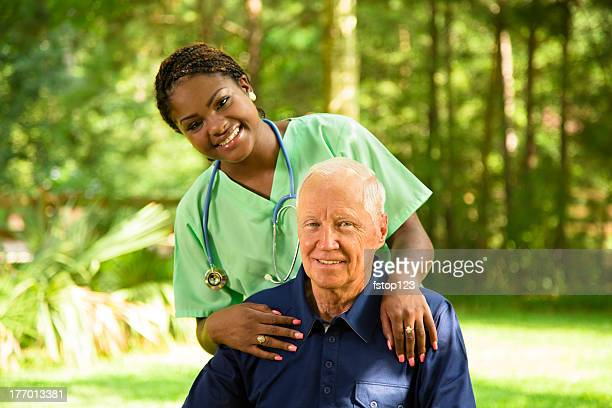 Medical:  Happy Caregiver visiting with senior man sitting outside.