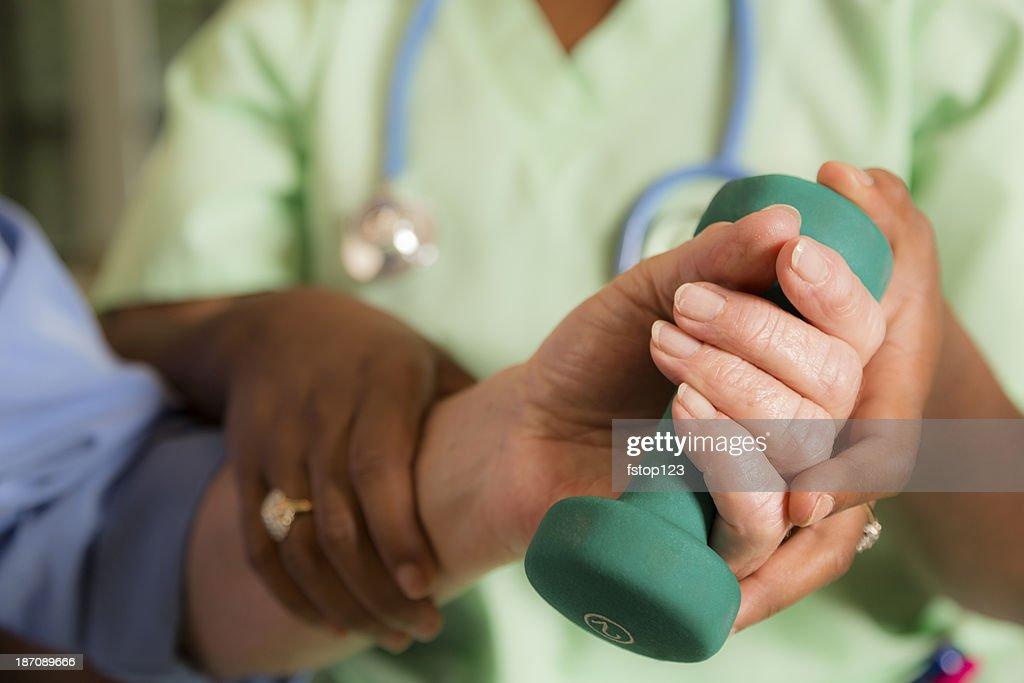Medicina: Casa medico infermiera aiutando donna esercizio dopo il polso intervento chirurgico. : Foto stock