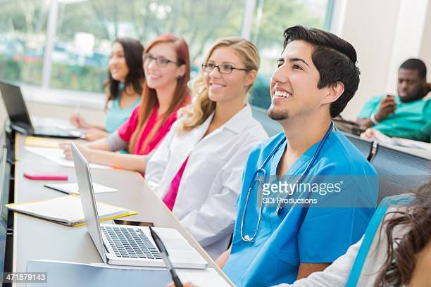 Medical interns or nursing students taking class in college classroom