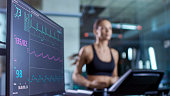 Medical Monitor Shows EKG Reading of a Woman Athlete Running on a Treadmill. Focus on Monitor.