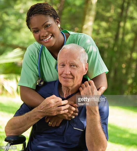 Médecine: Infirmière donnant une étreinte patient senior en fauteuil roulant.