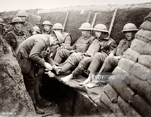 Medical officers attending to the feet of French soldiers in the trenches on the front line during World War One circa 1915