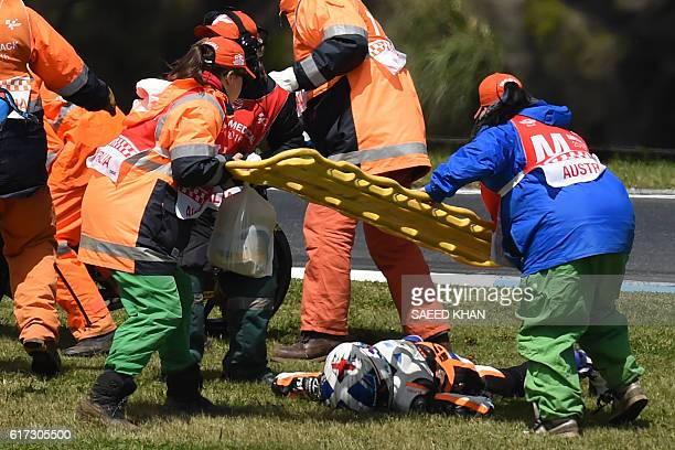 Medical officials prepare to move Peugeot MC Saxoprint's British rider John McPhee to an ambulance after he crashed during the Moto3 race at the...