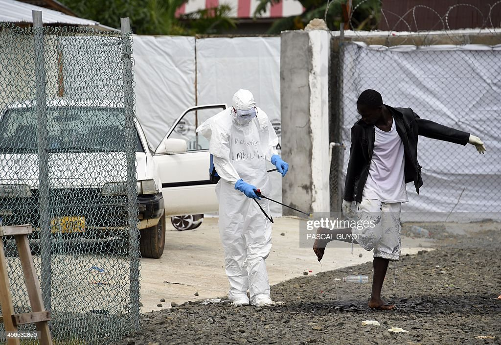 Medical personnel at the Ebola treatment centre at Island hospital in Monrovia disinfect people who had brought patients suspected of having the...