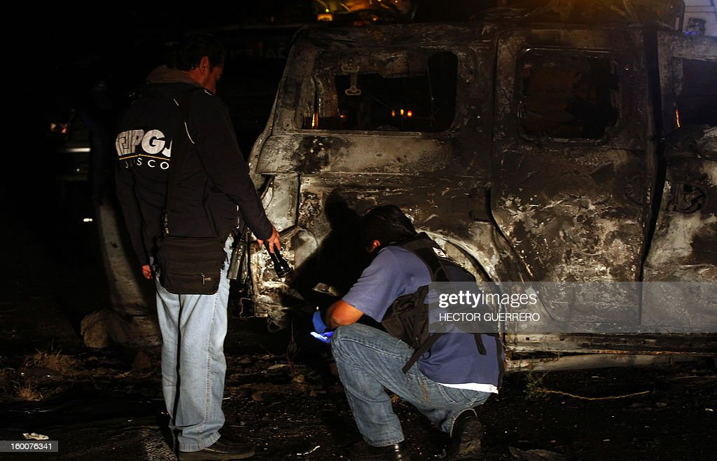 Medical personnel inspect a charred body inside a vehicle in Magdalena, Jalisco State, Mexico on 25 January 2013. Five innocent civilians lost their lives during a clash between gangs of organized crime. AFP PHOTO/Hector Guerrero