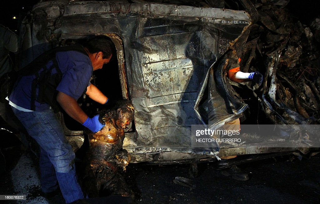 Medical personnel remove a charred body from a vehicle in Magdalena, Jalisco State, Mexico on 25 January 2013. Five innocent civilians lost their lives during a clash between gangs of organized crime. AFP PHOTO/Hector Guerrero