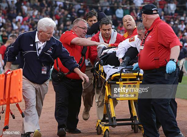 Medical personnel remove a fan injured by a broken bat in the second inning The Boston Red Sox take on the Oakland Athletics in Game 1 of a three...