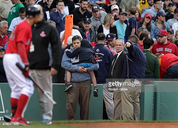 Medical personnel remove a fan injured by a broken bat in the second inning Larry Lucchino President and CEO of the Boston Red Sox was also on the...