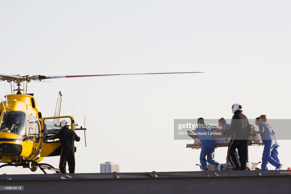 Medical personnel rushing patient to helicopter