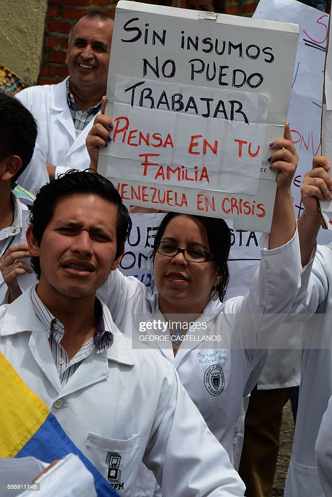Medical personnel with a sign reading 'Without supplies I can't work. Think of your family. Venezuela in crisis', demonstrate in rejection of the policies conducted by the government of Venezuelan President Nicolas Maduro in the border town of San Cristobal on May 30, 2016. The shortage of medicines in Venezuela exceeds 85%, revealed the president of the farmaceutical federation of Venezuela, Freddy Ceballos. / AFP / George Castellanos