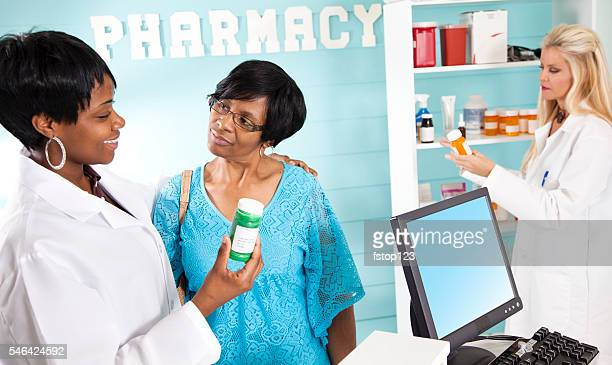 Medical: Pharmacist discusses prescriptions in pharmacy. Customer.