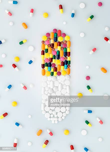 Medical pills and tablets in shape of drug capsule and scattered