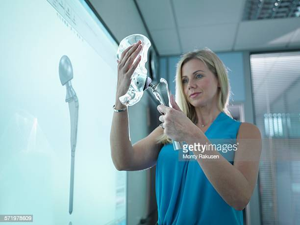 Medical product designer inspecting hip joint model with graphical screen
