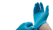 Medical professional and hospital staff concept with surgeon, doctor or nurse putting on blue surgical gloves isolated on white background with clipping path and copy space