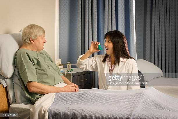 Medical professional demonstrating inhaler to patient