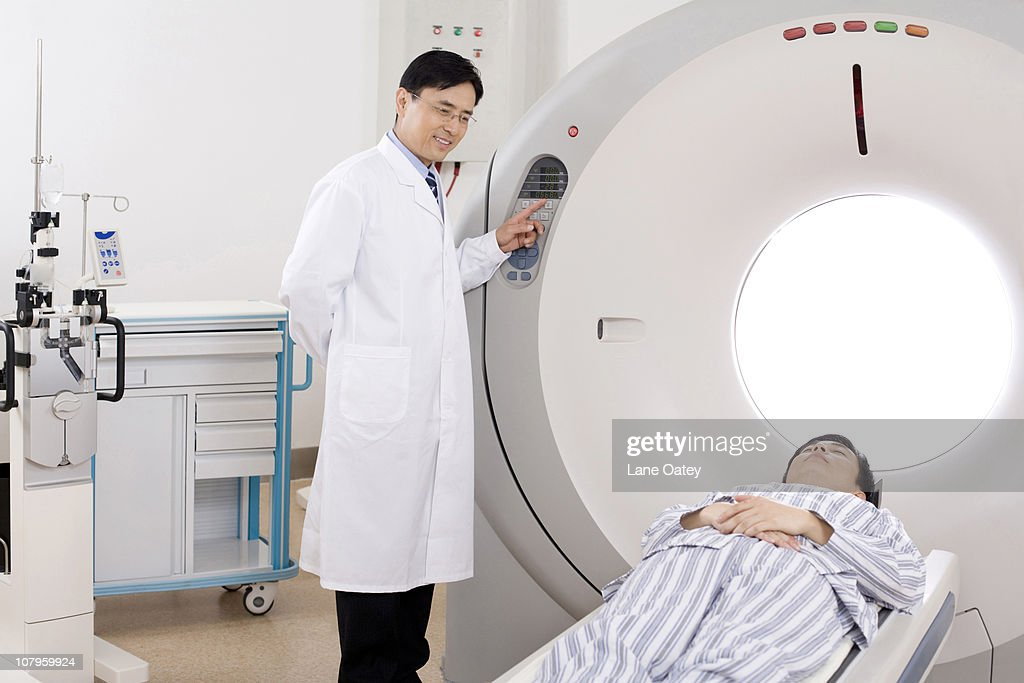 Medical professional helping a patient into a MRI scanner : Stock Photo