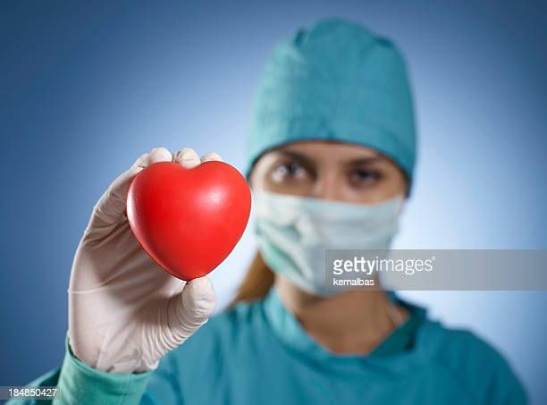Medical professional on scrubs holding up red heart