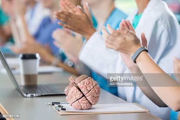 Medical professionals applaud during seminar