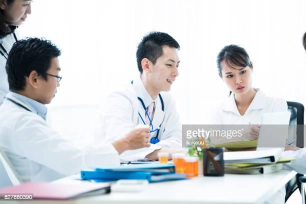 Mediziner sprechen von Tabletten in der orange Glas auf der medizinischen Konferenz.