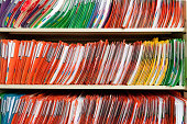 Horizontal image of a filing cabinet full of medical records. The files folders are in various bright colors.