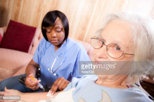 Medical: Senior woman receives injection from home healthcare nurse. : Stock Photo