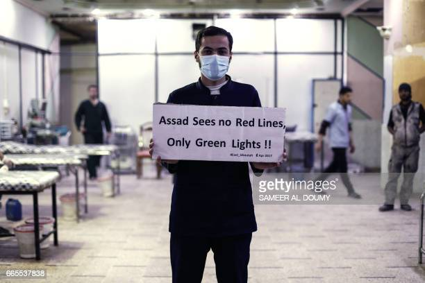 A medical staff at Damascus Countryside Specialised Hospital holds a placard condemning a suspected chemical weapons attack on the Syrian town of...