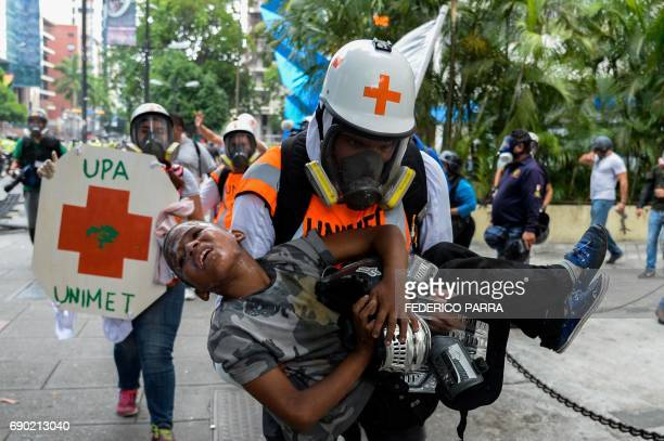 Medical staff carry a boy suffering from the effects of tear gas during clashes between opposition demonstrators and the riot police during a protest...