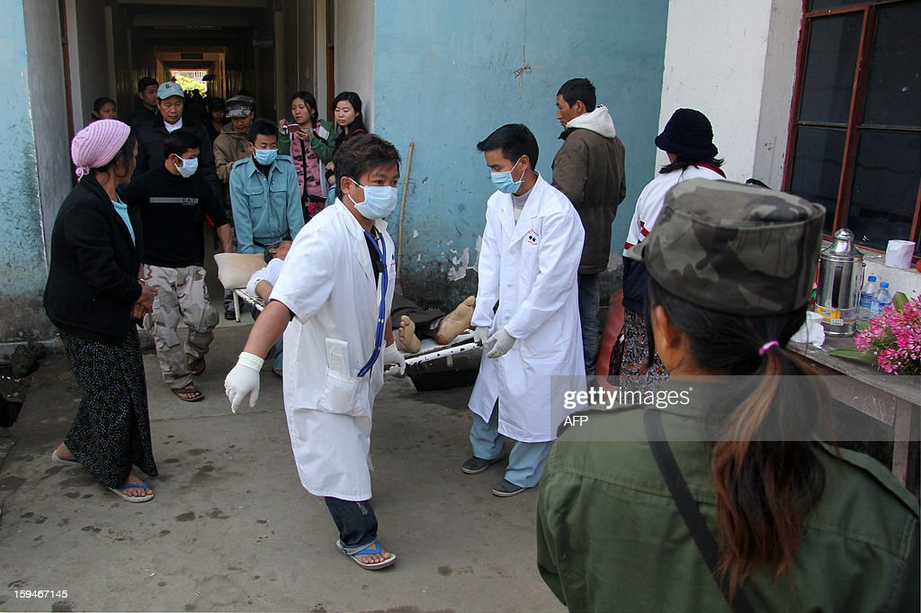 Medical staff carry a man (C) on a stretcher after he was injured during an artillery attack in the morning in downtown Laiza, at the Kachin Independence Army Headquarters, at Laiza hospital, in Laiza on January 14, 2013. Kachin rebels in Myanmar said three civilians were killed and six wounded on January 14 in the first government attack on their stronghold, as fighting escalated in the country's last active civil war. AFP PHOTO / Tony NEIL