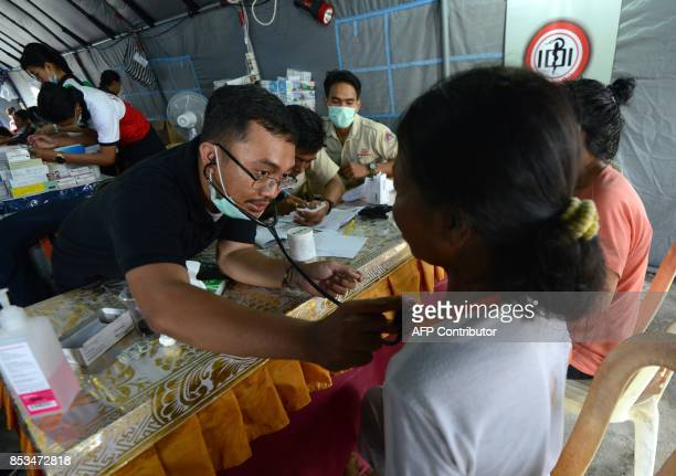 A medical staff checks a woman at an evacuation centre in Klungkung regency on the Indonesian resort island of Bali on September 25 2017 Authorities...
