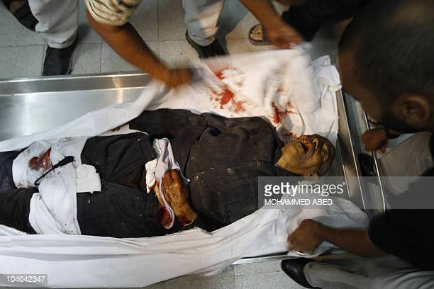 Medical staff cover the body of 91yearold Palestinian farm caretaker Ibrahim Abdullah Abu Saeed killed on September 12 2010 by Israeli gunfire in the...