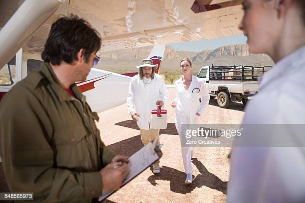 Medical staff delivering supplies in cooler box by plane, Wellington, Western Cape, South Africa