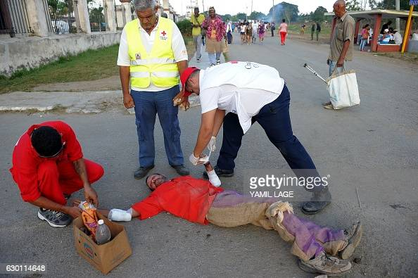 Medical staff help a Cuban pilgrim that was crawling to St Lazarus Church in El Rincon 25 km from Havana on December 16 while celebrating one of the...