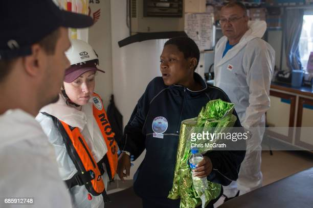 MOAS medical staff help a woman who suffered cardiac problems disembark the Migrant Offshore Aid Station 'Phoenix' vessel on May 20 2017 in Trapani...